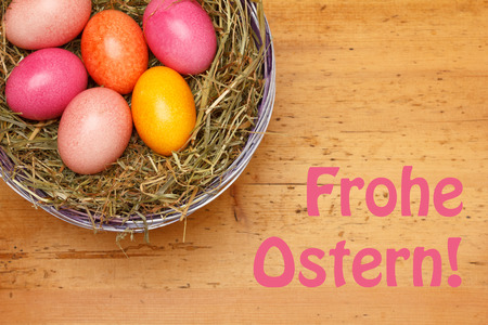 frohe: Text Happy Easter in german, Frohe Ostern, with 6 Easter Eggs in a basket with straw on a vintage wooden background Stock Photo