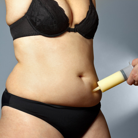 hand bra: Body of a middle aged rotund woman in bra and pants with a male hand holding a syringe with fat sucked out of her belly, liposuction, square format