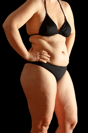 excessive: Body of a middle aged woman in bikini with excessive fat on waist and thighs, dimpled skin, black background