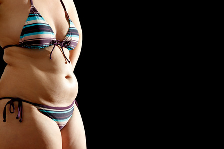 overeat: Womans body in bikini with fat rolls on waist and belly on black background, text or copy space
