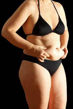 black hand: Woman in bikini with flabby stomach holding the excessive fat in her hands, black background Stock Photo