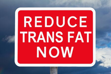 Red and white signpost REDUCE TRANS FAT NOW in front of a dark sky, symbol for health risk, spoof of british road signs