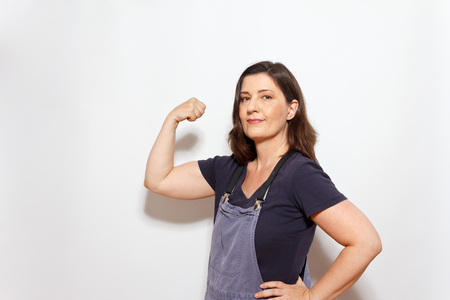 Middle aged woman in dungarees with one hand on her hip and flexing the biceps muscles of the other arm, white background