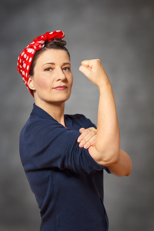 Strong and confident woman with a red headscarf and a clenched fist, vintage or retro effect of the 40s in America, gray background, copyspace Standard-Bild