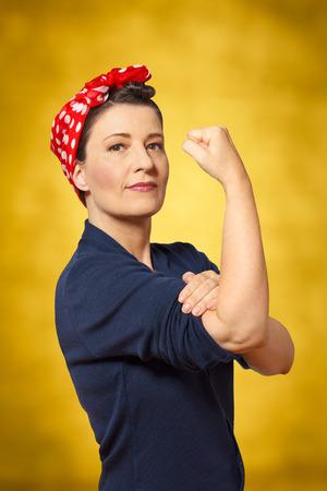 Vrouw met een rode hoofddoek en een gebalde vuist, vintage of retro effect van de jaren '40 in Amerika, gele achtergrond, copyspace, teken voor vrouwen macht Stockfoto