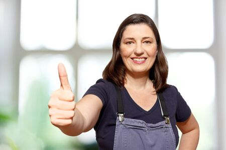 Middle aged female gardener  or saleswoman in DIY store in bib overall showing the thumbs up sign, blurry white and green background, copy space