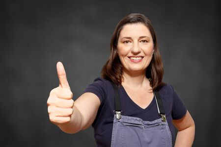 bib overall: Mature woman worker in bib trousers holding her thumb up and smiling happily, black or dark background, copyspace, copy space