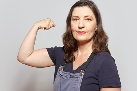 dungarees: Middle aged and self-confident woman in dungarees flexing her biceps muscles, white background
