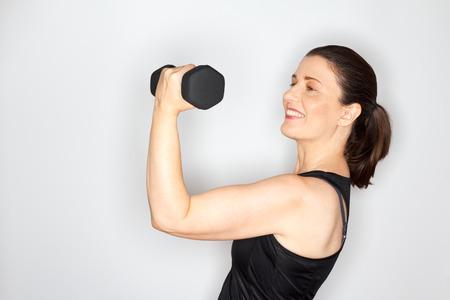 Blij en trots vrouw van middelbare leeftijd in een zwarte muscleshirt hijs halter, lichte achtergrond, kopieer ruimte
