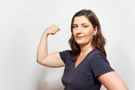 Middle aged woman flexing her biceps muscles, showing self-confidence and pride, white background Stock fotó