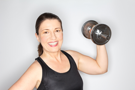 Happy and proud middle aged woman in a black sports top lifting heavy dumbbell, light background, copy space