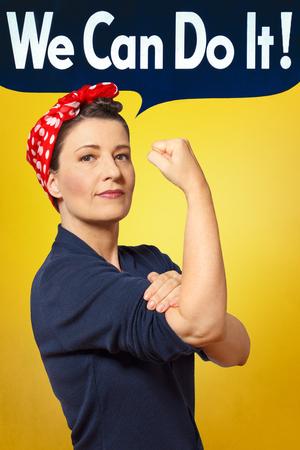 Possiamo farlo bolla testo in foto di una donna forte e fiera con un foulard rosso rimboccarsi la manica, tributo perfetto al classico manifesto americano di Rosie la rivettatrice Archivio Fotografico - 60220614