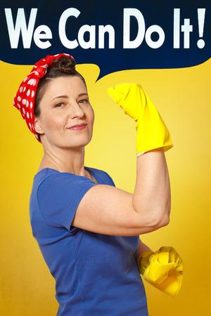 Vrolijke vrouw reiniger met rode hoofddoek, gele schoonmaak handschoenen en doek, houdt haar arm en tonen haar spieren, eerbetoon aan de Klinkhamer Rosie Stockfoto