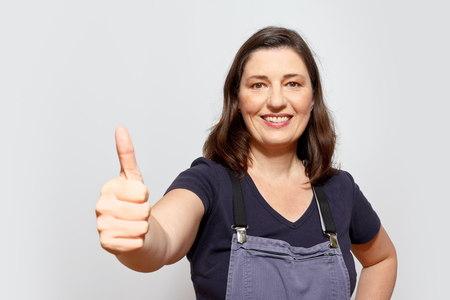 bib overall: Smiling adult woman wearing dungarees showing the thumbs up sign, light background, copy space