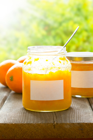 marmelade: Homemade orange marmelade in jam jars, one with an open lid and a spoon inside, on a dark wooden table with an orange tree in the background on a sunny summer day, copyspace Stock Photo