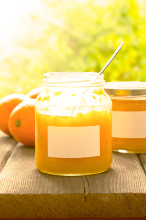 marmelade: Homemade orange marmelade in a jam jar, open lid and spoon inside, on a dark wooden table in bright summer sun, vintage filter effect, copyspace Stock Photo