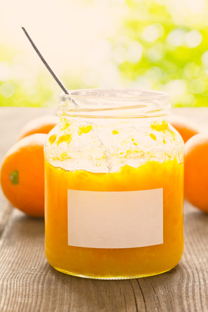 marmelade: Home made orange marmelade in a jam jar, open lid and spoon inside, on a rustic wooden table in bright summer sun, retro filter effect, copyspace Stock Photo