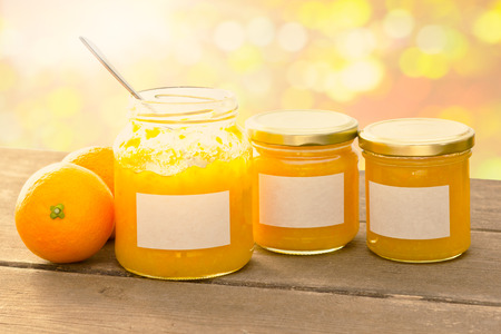 marmelade: Homemade orange marmelade in jam jars, one with an open lid and a spoon inside, on a dark wooden table with a blurry background in summer sunlight, retro filter effect, copyspace