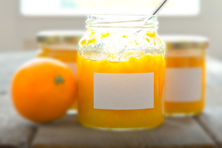 Three jars of homemade orange marmalade with white labels, one with an open lid and a spoon inside, and one fresh orange on a old kitchen table,  soft focus effect, copyspace, text space