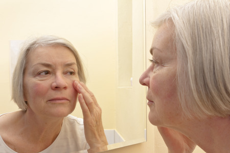 Senior woman with grey hair having a close look at the wrinkles of her facial skin in a mirror, yellow background