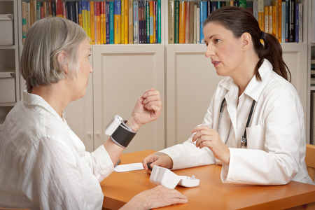 exact position: Female doctor explaining the correct use of a wrist blood pressure monitor to her elderly patient to reduce the risk of an heart attack or stroke Stock Photo