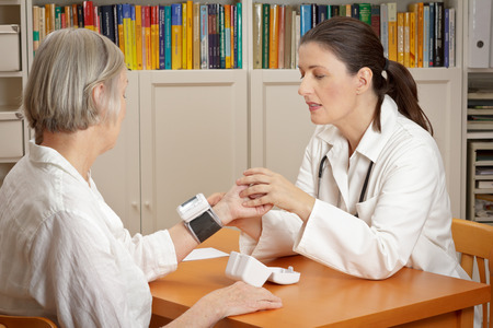 Middle aged doctor explaining the correct use of a wrist blood pressure meter to her senior female patient in order to reduce the risk of an heart attack or stroke