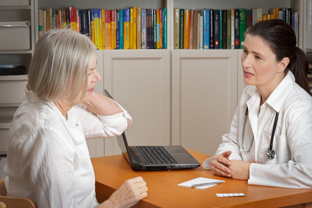 Old woman consulting an empathic female doctor considering acute neck pain caused by muscular tension Stock fotó