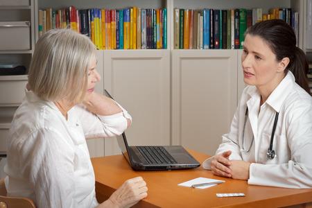 Oude vrouw overleg met een empathische vrouwelijke arts overweegt acute pijn in de nek veroorzaakt door spierspanning