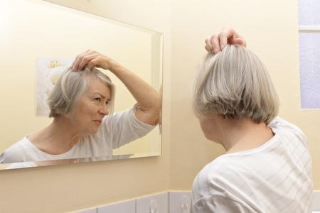 calvicie: Mujer mayor con el pelo gris fina y una mirada de preocupación en su rostro que examina su calvicie comienza en el espejo de su cuarto de baño de color amarillo
