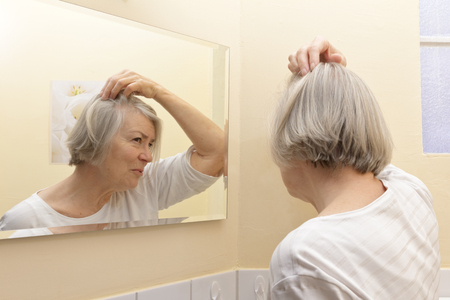 Old woman with thin gray hair and a worried look on her face  examining her beginning baldness  in the mirror of her yellow bathroom