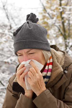 Senior woman with scarf and hat in a winter jacket blowing her nose into a paper tissue in front of a tree with snow Stock Photo