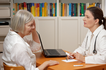Female middle aged doctor in white coat listening attentively to an old woman with headache or migraine