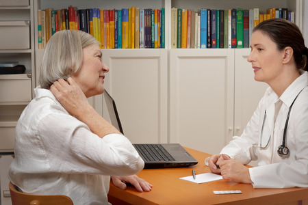 Senior female patient consulting middle aged doctor because of strong neck pain caused by muscular tension