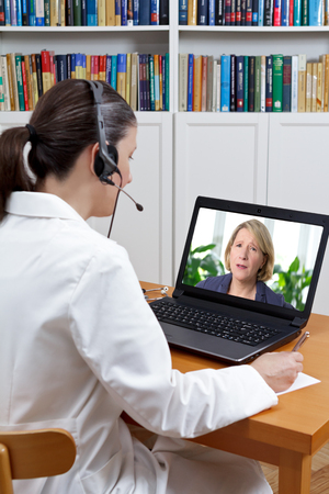 Doctor at a pain management center in her office with headset and laptop, listening to patient in agony with strong backache, telemedicine concept