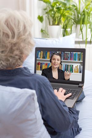 Achter mening van een oude vrouw zitten met laptop op de bank van haar woonkamer, een videochat met haar advocaat via internet, online juridisch advies