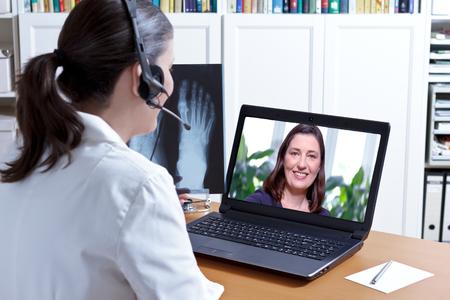 Vrouwelijke arts in haar operatie kantoor met een koptelefoon in de voorkant van haar laptop, een röntgenfoto van een voet in de hand, praten met een patiënt, e-health-concept