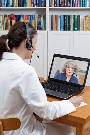 Doctor of geriatrics sitting at the desk of her office with headset and laptop, talking to an old patient via skype, telehealth concept 免版税图像