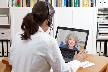 Female doctor of geriatrics in her surgery office with headset in front of her laptop talking via video call with an old patient about her prescribed drugs