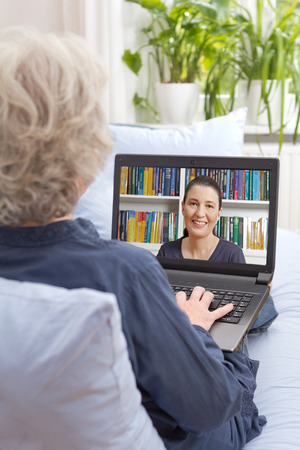 Senior woman sitting with laptop on the sofa of her living room, having a video call with her daughter via the internet, rear view