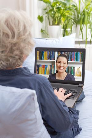 Senior vrouw zitten met laptop op de bank van haar woonkamer, met een videogesprek met haar dochter via het internet, achteraanzicht