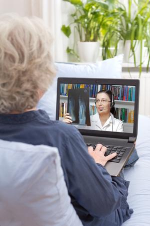 Achter mening van een senior vrouw zitten met laptop op de bank van haar woonkamer, met een videogesprek met haar arts via internet, online overleg, e-health