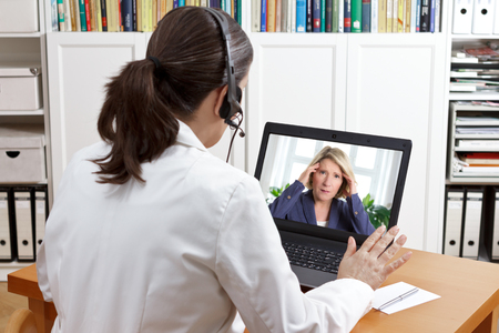 Vrouwelijke arts of apotheker in haar operatie kantoor met een headset voor haar computer praten via videochat met een patiënt, vertelt haar om dingen makkelijk te maken