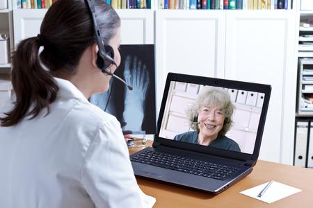 Vrouwelijke arts in haar operatie kantoor met headset in de voorkant van haar laptop, een röntgenfoto van een voet in de hand, praten met een senior patiënt, telemedicine-concept