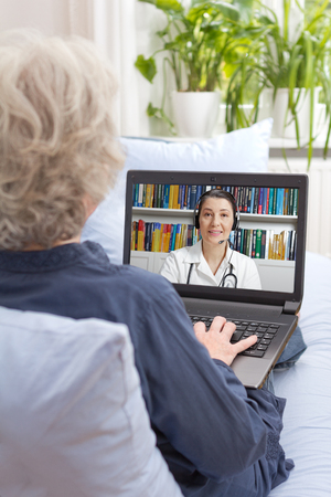 Rear view of an old woman sitting with laptop on the sofa of her living room, having a video call with her physician via the internet, telemedicine, telehealth