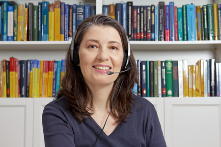 Friendly middle aged woman with blue t-shirt and head set in an office with lots of books having an live video call via the internet, telelearning, e-education Stock Photo