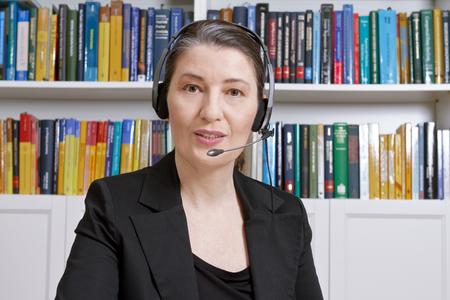 Vriendelijke vrouw van middelbare leeftijd met koptelefoon en zwarte blazer in een kantoor met veel boeken, praten met iemand via internet, tele marketing of verkoop