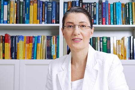 Mature woman in white blazerin front of books explaining something, professor, teacher, private tutor, coach, counselor, adviser, therapist