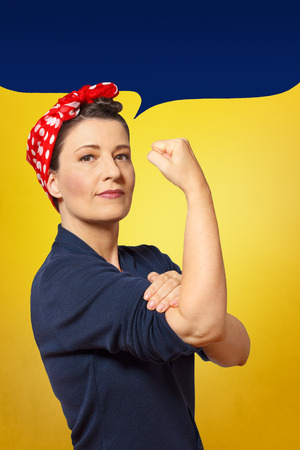 Stoere en zelfverzekerde vrouw met een gebalde vuist die haar mouw oprolt, lege tekstballon met tekstruimte, eerbetoon aan het Amerikaanse pictogram Rosie Riveter