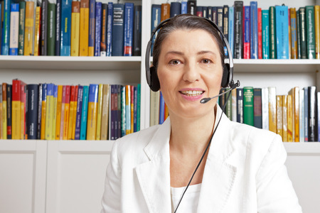 Friendly middle aged woman with headphones and white blazer in front of a bookshelf in her study, having a live chat via the internet, online tuition