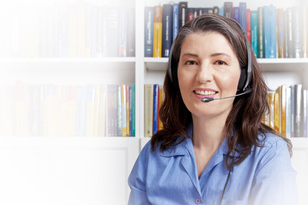 Middle aged woman with headset in a blue shirt in front of lots of books, telephoning via the internet as seen through the webcam, white copy space